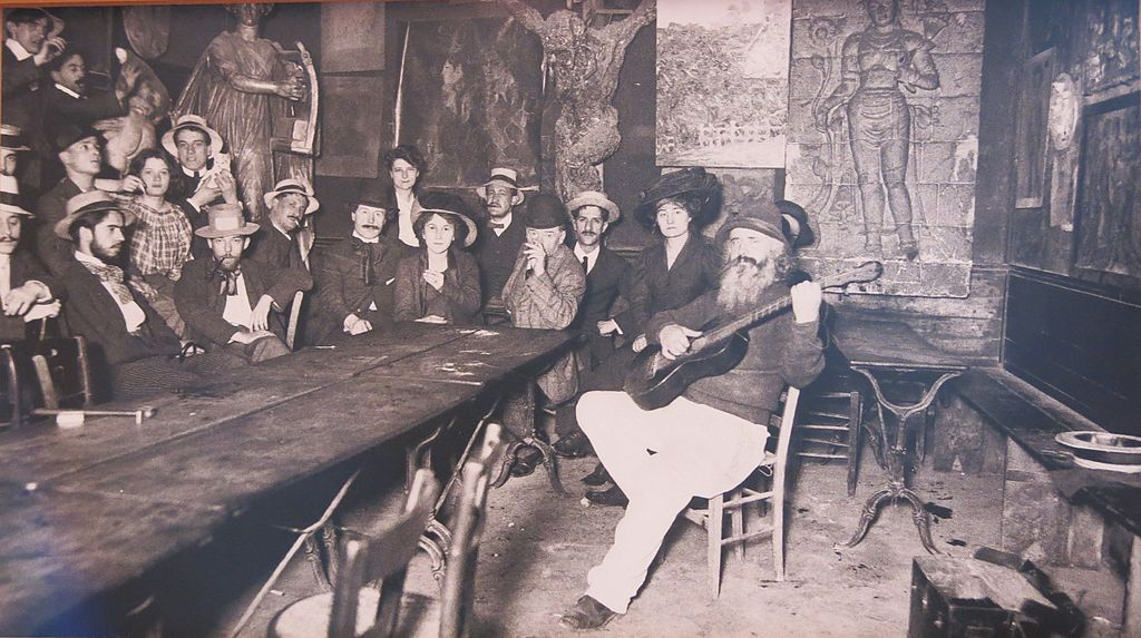 Frederic Gerard known as Frede the landlord of the Lapin Agile cabaret in Montmartre plays the guitar on front of an attentive audience gathered around a table. The room is sparsly decorated with wooden chairs and tables. In the background Picasso's painting of a harlequin and companinion known as At the Lapin Agile can be seen on the wall.