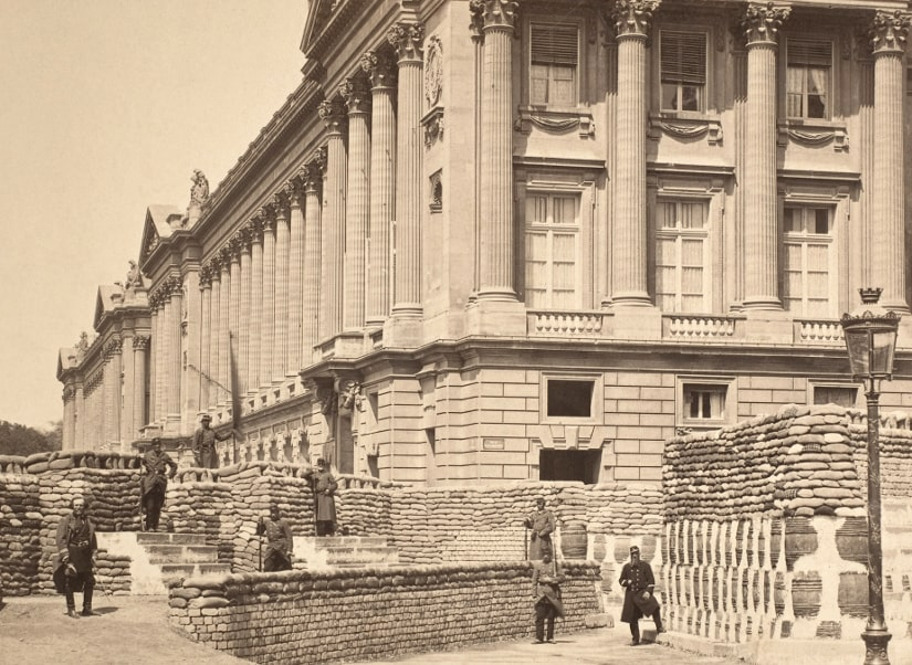 Black and White contemporary photograph by Auguste Hippolyte Collard of Communard barricades from the Paris Commune of 1870 – 1871. View of fortified barricades on the junction of Rue Royale and Place de la Concorde, Paris. Some Communard soldiers stand on front of barricade posing with rifles.