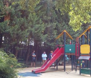 Children playing on a slide in jardin Burq in Montmartre. The garden is to the rear of the Bateau Lavoir artists'studios. Their parents look on