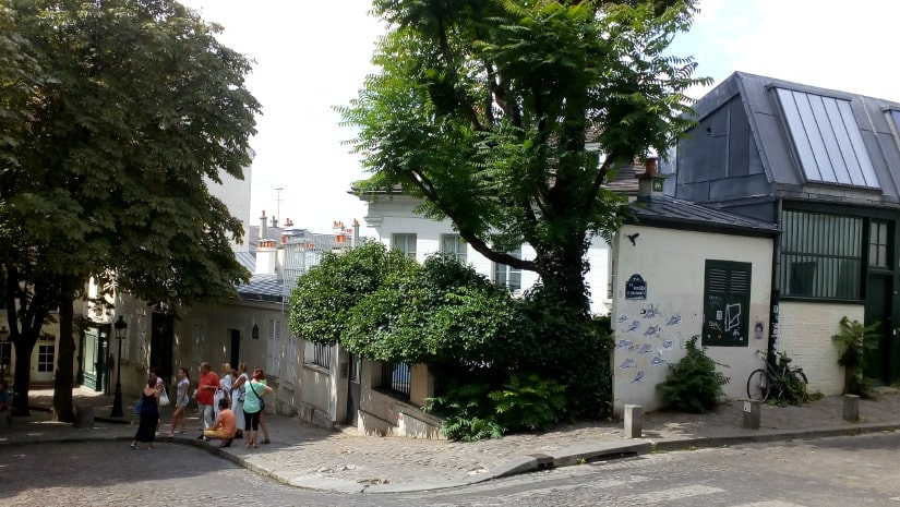 A general view of the Bateau Lavoir artists studios and workshops. The view is from Rue Ravignan looking west. Some tourists and visitors are visible.