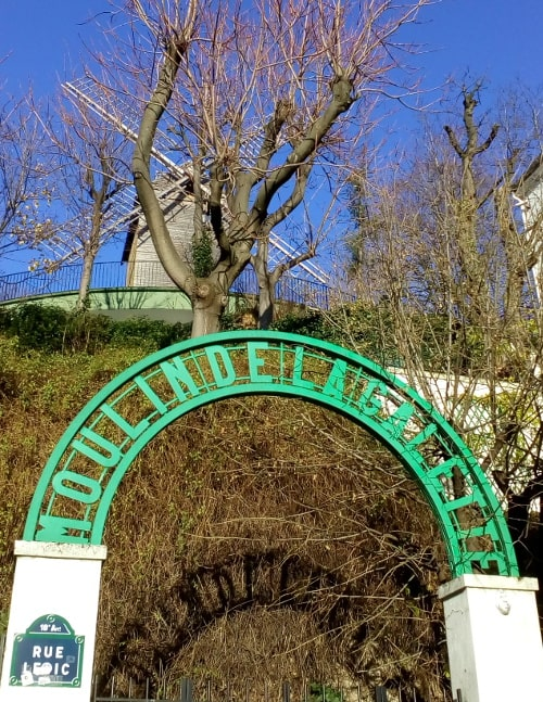 The Blute-Fin windmill stands on the top of Montmartre in some gardens. The windmill is set behind some trees and is framed through an arched green sign announcing the Moulin de la Galette. The view is from below in Rue Lepic 75018 Paris.