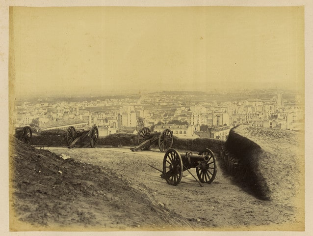 Black and White contemporary photograph by Bruno Braquehais of four cannons on Montmartre Hill overlooking Paris. The cannons aim in different directions over Paris.