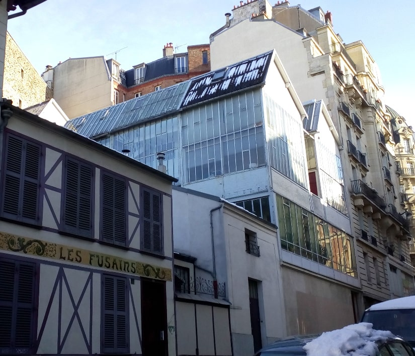 A view of the artists studios Cité des fusains from the Rue tourlaque Paris 75018. There is some snow on the cars in the foreground and on the glass studios.