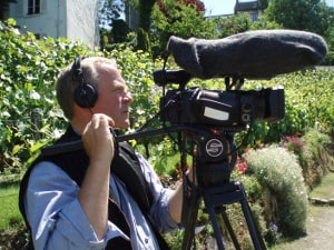 The documentary film maker stephen Macmillan seen filming with camera and sound recording equipment in the Clos Montmartre vineyard.