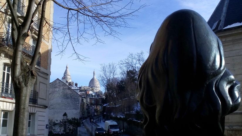 The bronze bust of French singer Dalida looks towards the Sacre Coeur Montmartre. The view is from behind her head. In the distance we see the dome of the Sacré Coeur Paris.