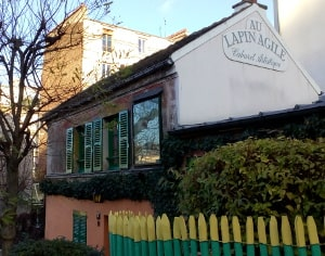 The Lapin Agile cabaret Montmartre. A modest one story building with some trees in front surrounded by a green and yellow rustic fence. A famous Montmartre cabaret of the early 20th century. Rue des Saules 75018 Paris