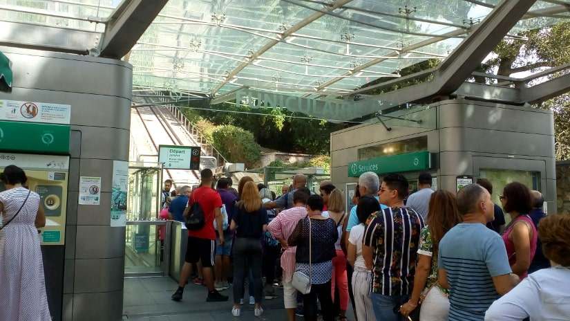 Tourists queueing for the funicular railway at the foot of Montmartre in summer.