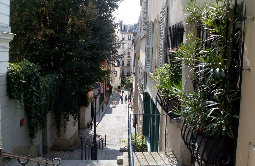 Looking down Rue André Antoine from Rue des Abbesses Montmartre. A series of stairs leads down to a narrow street fringed by shuttered buildings and plants. Railings and a traditional gas type street light can be seen in foreground.