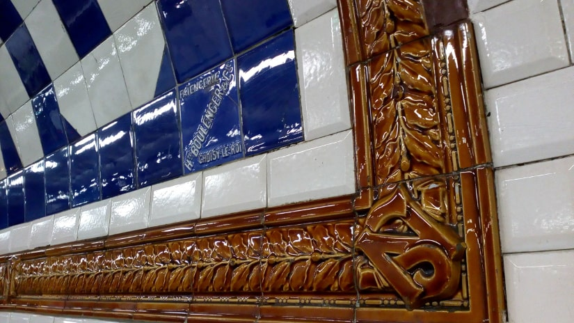The detailed ceramic work around the station names on the old North South métro line. A brown ceramic tile bears the initials NS. Further ceramics surround the station name which is picked out in blue tiles on a white background. The North South line dates from 1911 and is now known as line number 12.