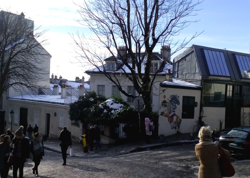 A general view of the Bateau Lavoir artists studios and workshops. The view is from Rue Ravignan looking west. Many tourists and visitors are visible.