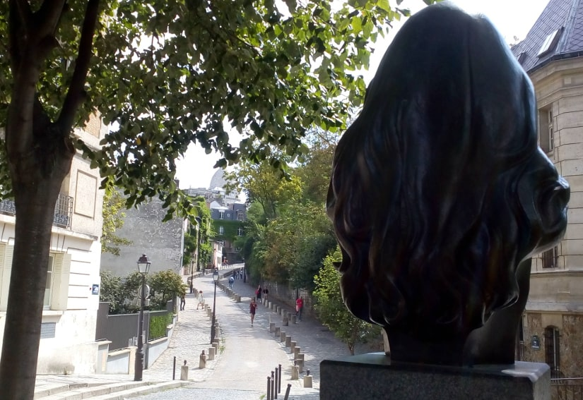 A view of the winding Rue de l'Abreuvoir Montmartre with in the foreground the back of the bust of the French singer Dalida in Place Dalida Montmartre.