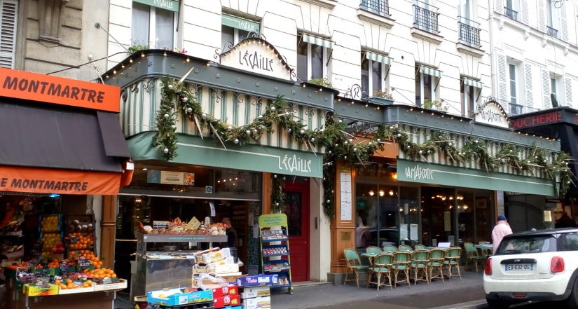 Rue des Abbesses is a lively street in the heart of Montmartre. It features many cafés and small businesses. The view shows a restaurant and a corner shop with fruit piled at the entrance.