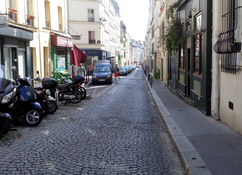 Rue des Trois Freres Montmartre showing a straight street with a steady incline. The street is fairly narrow and cobbled apartment blocks and small businesses line the streets the buildings are about five stories high.