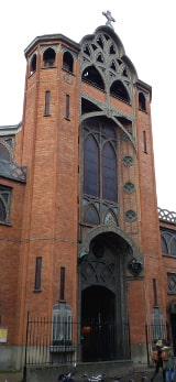 A church featuring a tall brick tower in the Byzantine style featuring Art Nouveau details of crosses and religious symbols. The church is the first to feature a structure of reinforced concrete which allows the slender pillars and arches inside.