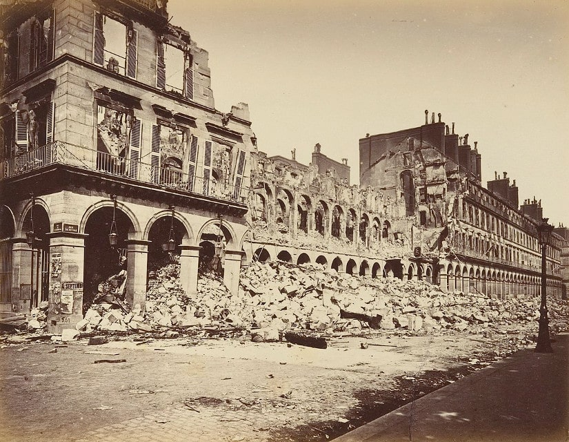 Black and White contemporary photograph by Alphonse J Liébert of the damage on Rue de Rivoli. The photograph shows destroyed and partially destroyed buildings with the fallen debris on Rue de Rivoli. The debris reaches to the top of the Rue de Rivoli arches.