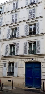 A view of a typical 4 storey white Parisian apartment block. The windows have shutters. Theo and Vincent van Gogh lived here in 1886-1888.
