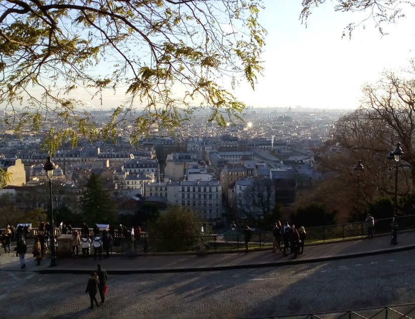 View of Paris from the Montmartre Hill. Viewpoint is from on front of Sacré Coeur church. Distant Paris rooftops are lit up by weak winter sun