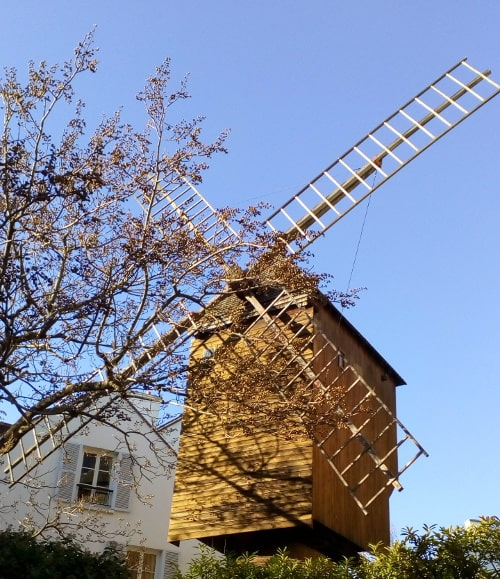 The Radet windmill framed against a clear blue sky over the entrance to the Moulin de la Galette restaurant Rue Lepic Paris 75018
