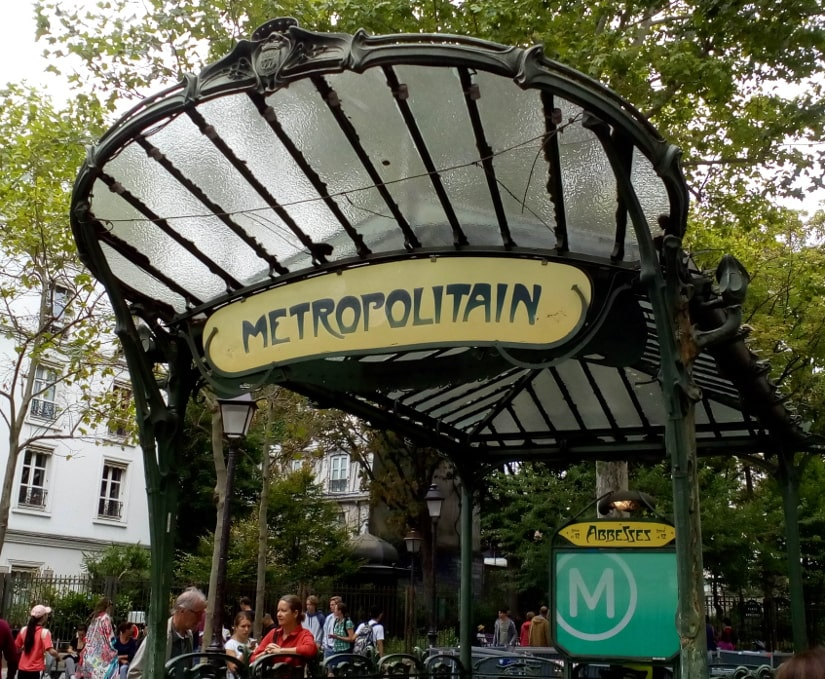 The Art Nouveau entrance to the Abbesses metro in Montmartre Paris. A glass and wrought iron structure shelters the steps leading down to the metro. The green structure is set in a busy wooded square with many tourists around the entrance.