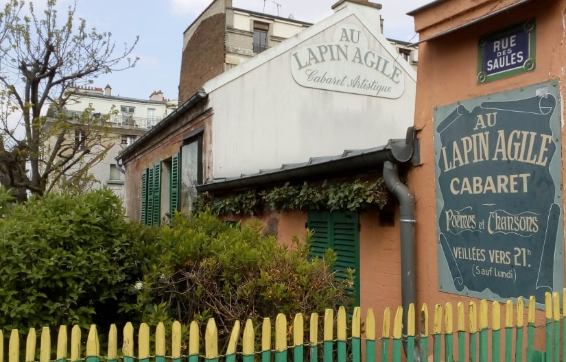 The Lapin Agile (Agile Rabbit) cabaret Rue des Saules Montmartre. A small one story building set in a small garden with green shutters on the windows. A sign in French tells us that this is the Lapin Agile cabaret, that it specialises in poetry and song and that it will open at about 21:00 except on Mondays. In the foreground is a fine decorative wooden fence painted in green with yellow tips.