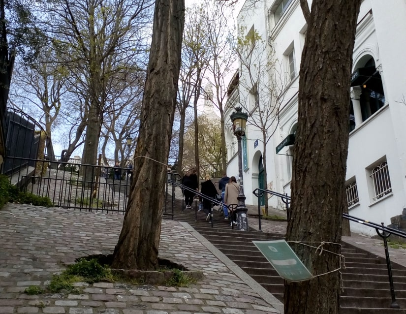 People climbing steep stairs, the Sacré Coeur dome can de seen in the background. Mature trees line the stairs, a traditional gas type street light can be seen in the middleground.
