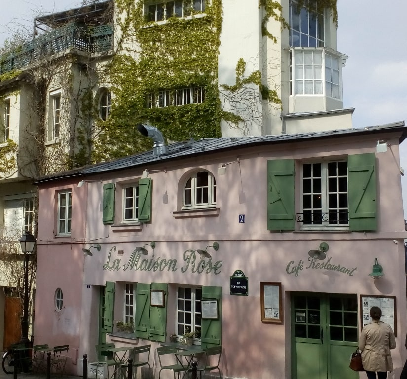A small pink restaurant known as the Pink House in Montmartre. The windows have green shutters and some tables are set on the pavement. Adjoining the building and set behind are some taller ivy clad apartment blocks with balconies and large artist studio style windows.