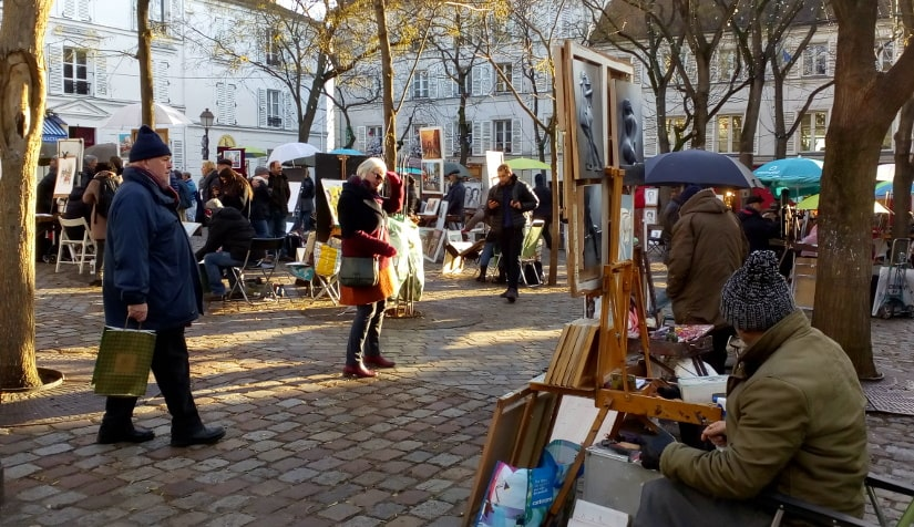 Place du Tertre Montmartre in winter. A painter sits with his paintings displayed on an easel. More painters can be seen behind sitting below umbrellas. In the middle ground tree trunks can be seen throughout the square and two tourists wander by the artist's stalls.