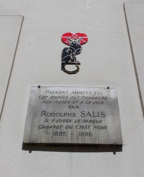 "A plaque on the side of the building at 12 Rue Victor Massé Montmartre which housed the second Chat Noir (Black Cat) cabaret. The cabaret existed between 1885 – 1896. Above the plaque is a tile cut out representing the image of a black cat made famous by Théophile Steinlen in his advertising poster for the cabaret. The plaque says: ""Passer-by, stop! This building was dedicated to the muses and to joy by Rodolphe Salis. It housed the famous Chat Noir cabaret 1885 – 1896."""