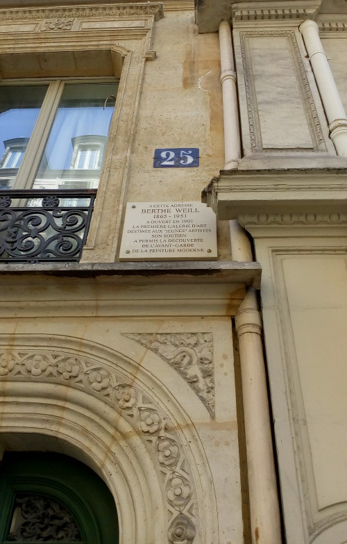 "The plaque and a detail of the doorway and apartment building at 25 Rue Victor Massé Montmartre. This was where Berthe Weill opened in 1901 her modern art gallery. The plaque reads: ""At this address Berthe Weill 1865 – 1951 opened, in 1901, the first art gallery for young upcoming artists. Her support facilitated the discovery of the avant-garde of modern art."""