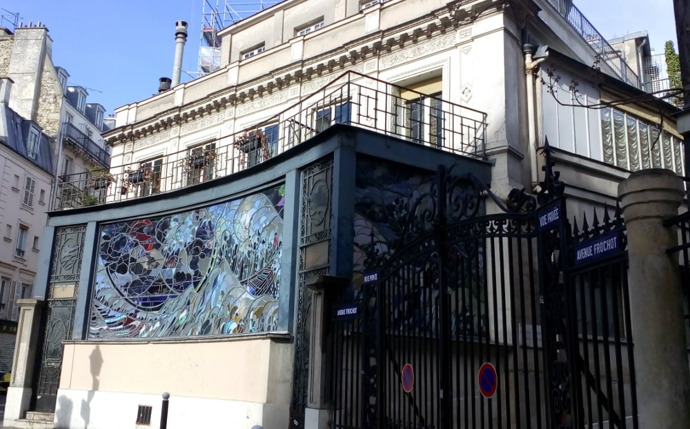 A view of a gated street and to the left a large framed stained glass window on the side of a building. The ornamental iron gates are in front of the private Avenue Frochot in Montmartre. The window the relics of an oriental styled cabaret.