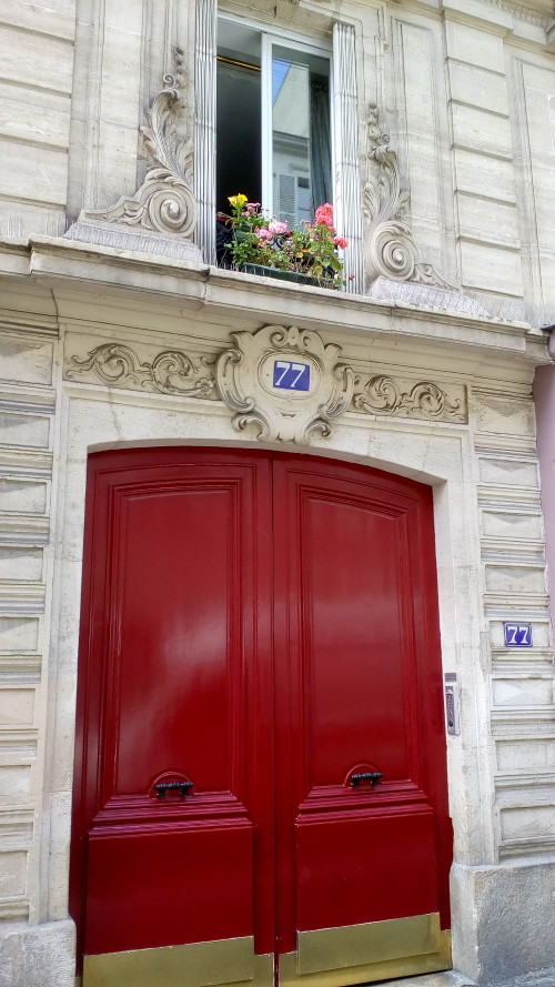 The bright red brass plated doors of 77 Rue Blanche Montmartre. This is one of Degas' many apartments and studios in Montmartre. The number 77 is prominently displayed on a blue background and a window is framed in some florid decorative carving. A flower box is visible on the window ledge.