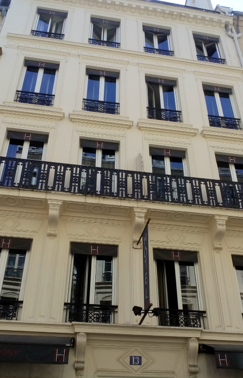 A view of a white painted four storey hotel facade at 13 Rue Victor Massé Montmartre. A wrought iron balcony and cornice runs across the facade on the second floor. The building is now a hotel but used to be Degas' apartment and studio in the 1860s.