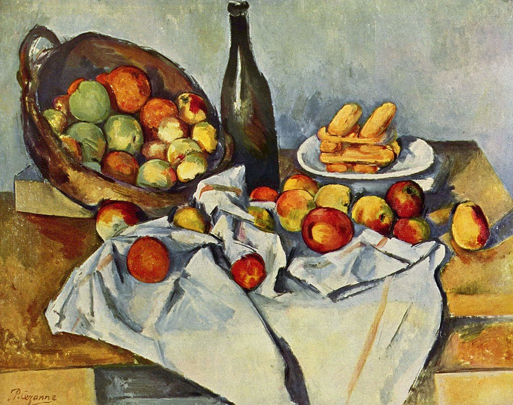 Paul Cézanne's still life of apples and pears on a table. An upturned fruit basket with apples and pears in it. Some of the fruit has been arranged on an untidy folded tablecloth. The picture is divided by a tall leaning wine bottle. The shape and composition of the fruit is evoked by the colour the artist has used rather than traditional modelling.