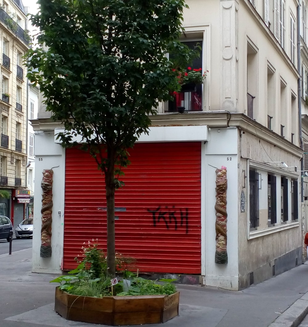 A closed shuttered red door with Chinese style decorations around it on front of which is a tree set in a small square. The building is the ground floor of an apartment block which forms the angle of Rue Jean-Baptiste Pigalle and Rue de la Rochfoucauld Montmartre. This is the site of le Grand Duc jazz night club in the 1920s