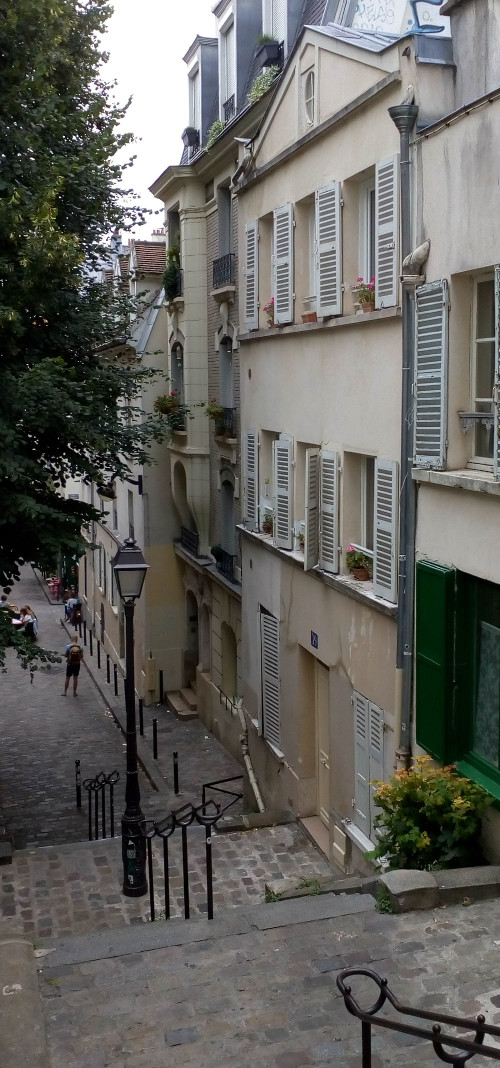 Steps leading to the narrow Rue André Antoine Montmartre Paris 75018. White buildings, a gas lamp, balconies, shutters and window plants. The building in the foreground is Georges Seurat's last studio in Montmartre.