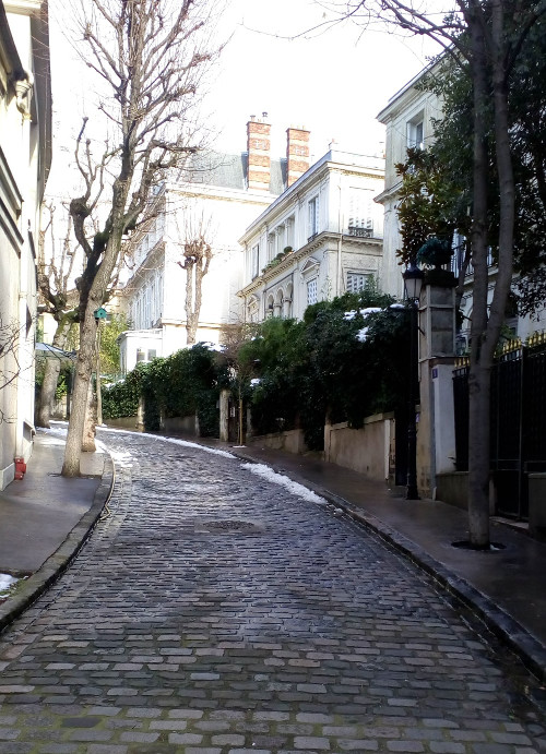 Looking up the curving cobbled Avenue Frochot in Montmartre. The avenue is tree lined and the large houses surrounded by gardens. Toulouse-Lautrec had a studio and apartment here in the late 1890s.