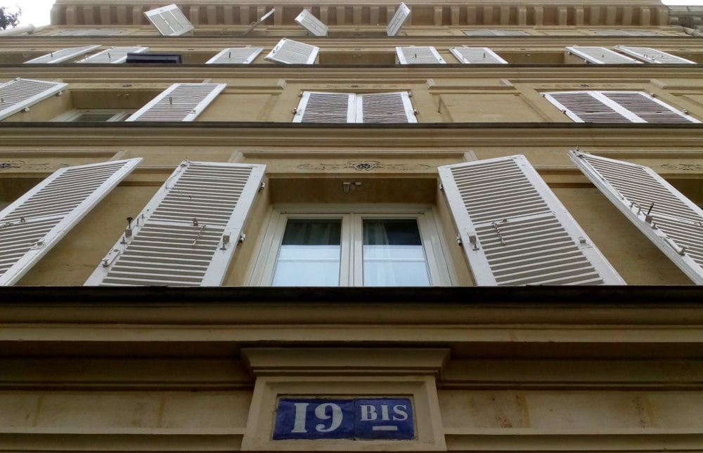 Looking up the facade of 19 Bis Rue Pierre Fontaine Montmartre. Windows and shutters are visible on the four storey building. Some shutters are thrown open. At the top is a cornice. The building is made from sandy yellow coloured stone.