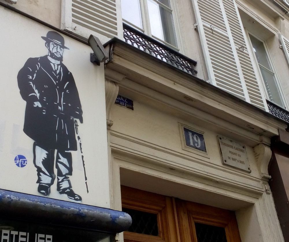 A stencilled image of Toulouse-Lautrec and cane stands next to the top of the door of his apartment at 19 Rue Pierre Fontaine Montmartre. Window shutters, the street number 19 and a plaque which tells us that Toulouse-Lautrec lived here are also visible.