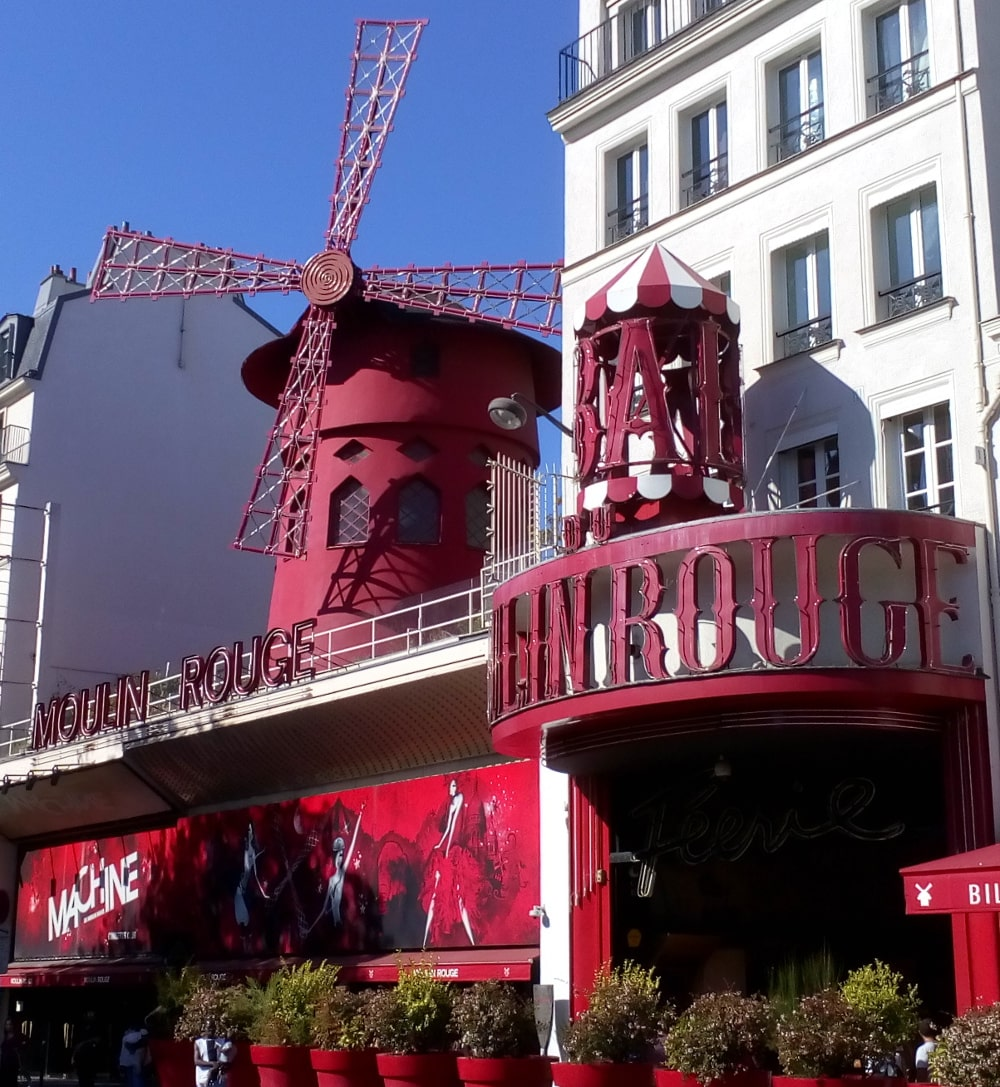 The Red facade, entrance and windmill of the Moulin Rouge in Montmartre. The red windmill is placed on the roof of the building. Bal and Moulin Rouge are displayed in large advertising letters. The scene is lit by bright autumn light.