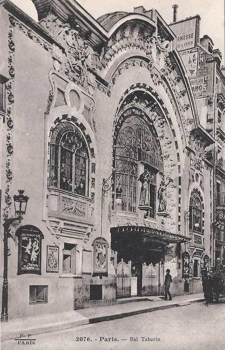 A huge arched window dominates the entrance to the Bal Tabarin. The building featured Art Nouveau sculpture and relief on the facade including two large smiling faces. A horse and cart are seen in front of the building as a man in a bowler hat enters.