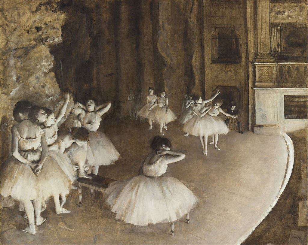 Ballerinas are rehearsing on stage. The stage is washed by strong stage lights which makes the scene seem black and white. In the foreground one group of dancers gather around a bench whilst in the background other dancers are rehearsing a scene under supervision.