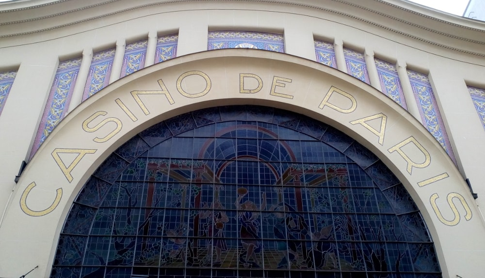 The white Art Deco stucco facade of the Casino de Paris concert hall. A large arched stained glass window dominates the facade. Casino de Paris is spelled out in large mosaic letters above the arch. Further blue mosaic decoration is visible above the arch. The arch movement is continued to the corniced roof giving a wave effect.