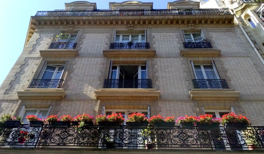 Degas 21 Rue Jean-Baptiste Pigalle. Looking up the facade of a brick and stone apartment building with a large balcony running across all of one floor. Flower boxes and flowers hang over the balcony. A large cornice is visible on the last floor on which runs another balcony.