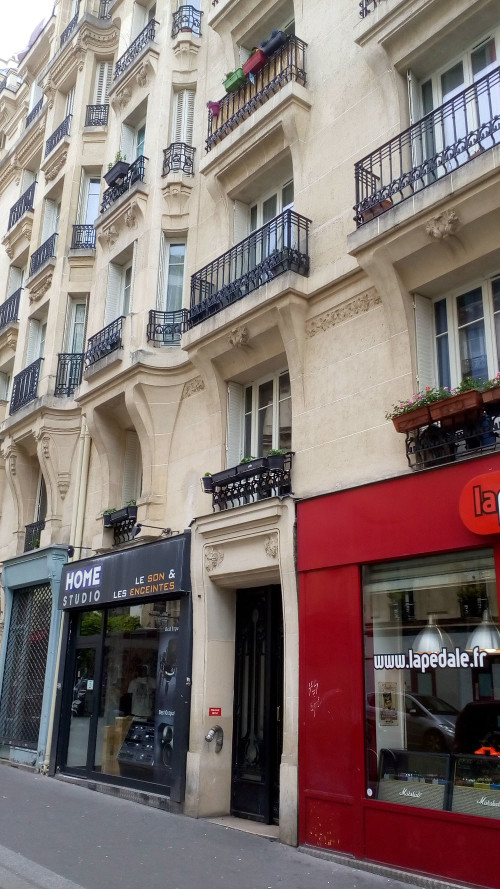 A rich bourgeois apartment building with wrought iron balconies, flower boxes and bow windows. The building is constructed from light coloured stone. Two small shop fronts flank the entrance to the building. The site at 37 Rue Victor Massé Montmartre of Degas' apartment and studio to 1912.