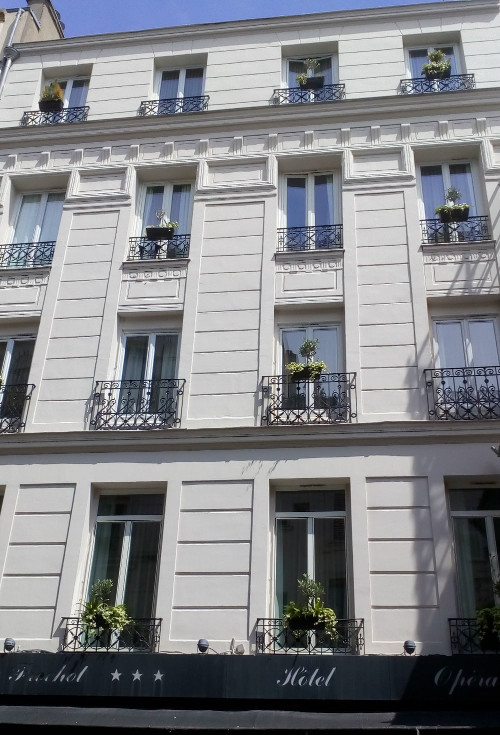 A view of a white painted four storey hotel facade at 4 Rue Frochot Montmartre. The building is now a hotel but used to be Degas' apartment and studio in the mid 1870s.