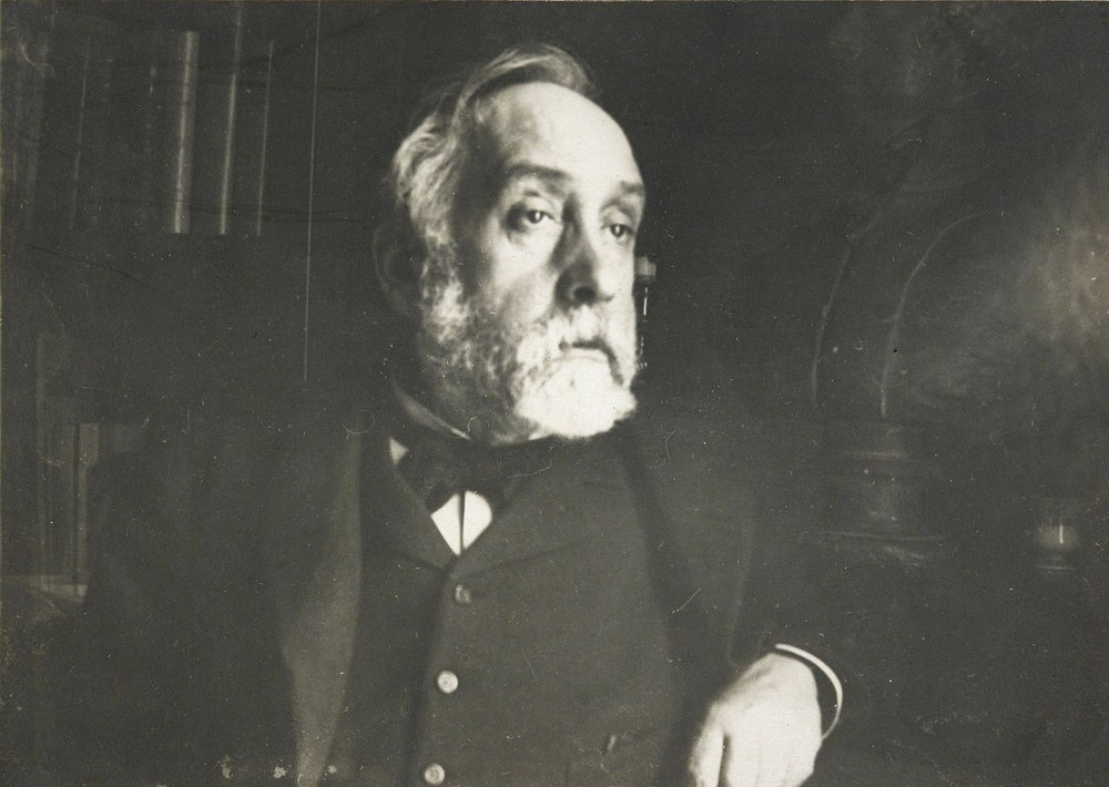 Degas' photographic self portrait from 1895. A bearded and solemn looking man looks to the viewers right. He is wearing a jacket, waistcoat and cravat. Some sombre details of furniture are just visible in background.
