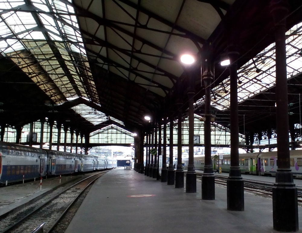 The Gare Saint-Lazare railway station in Paris. We see an empty curving platform, two trains, a line of iron pillars and huge station roof, part of which is made of glass to allow the daylight in. It is a dark winters day with no passengers in sight.