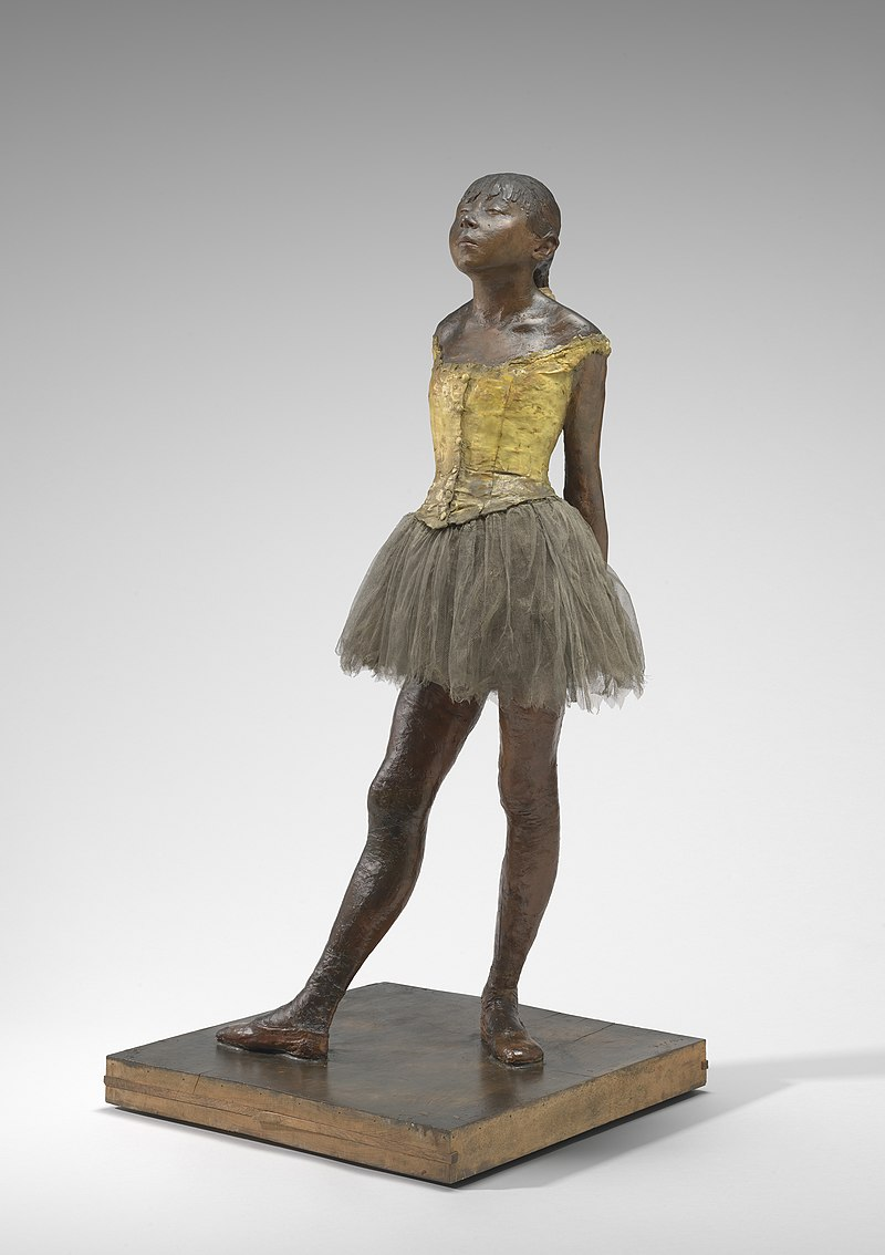 A bronze statuette of a ballet dancer assuming a rigid and contorted ballet pose. She wears a tutu, bodice and ballet shoes, she has real hair. Her face is upturned with a hint of defiance and pride in her expression.