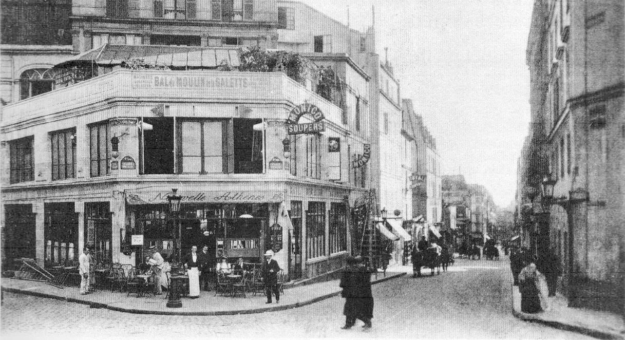 The Nouvelle Athènes (New Athens) café on Place Pigalle Montmartre. The image is from around 1900. A couple is seen seated outside the café, a waiter with a long white apron is nearby. Two workmen appear to be working on the building with high stepladders. A horse and cart approaches, coming up Rue Jean-Baptiste Pigalle. Two women are crossing the street and a man in a panama hit walks by.