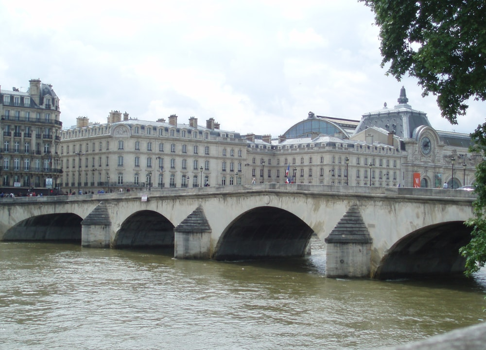 The Pont Royal bridge in Paris which links the Louvre Museum site to the nearby Orsay Museum. The stone arches of the bridge span the Seine. The nearby Orsay Museum is visible behind the bridge in this view looking south-west.